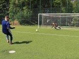 Zdjęcie przedstawiające piłkarza w niebieskim dresie oddającego strzał w kierunku bramki. W bramce bramkarz rzucający się w kierunku prawego słupka, w kierunku nadlatującej piłki.