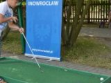 Zdjęcie przedstawia dziecko, które podjeło nieudaną próbkę trafień do dołka golfowego.